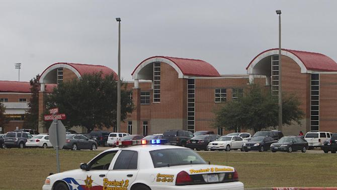 A police vehicle is parked near the entrance of North Shore High School after a shooting occurred Wednesday, Dec. 5, 2012, in Houston. Police say a high school student shot himself while in the back of a patrol car after being arrested earlier on suspicion of taking a gun to campus. (AP Photo/Houston Chronicle, Cody Duty)