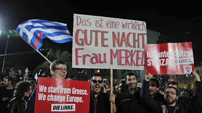 """Supporters of Germany's left-wing Die Linke party, hold placards as they show their support to Alexis Tsipras, leader of Syriza left-wing party after his speech to supporters in central Athens, late Sunday, Jan. 25, 2015. The placard, center, reads in German: 'This is really a goodnight Mrs Merkel' referring to the German Chancellor, and the right one reads: 'I support Syriza, Die Linke'. A triumphant Alexis Tsipras told Greeks that his radical left Syriza party's win in Sunday's early general election meant an end to austerity and humiliation and that the country's regular and often fraught debt inspections were a thing of the past. """"Today the Greek people have made history. Hope has made history,"""" Tsipras said in his victory speech at a conference hall in central Athens. (AP Photo/Lefteris Pitarakis)"""