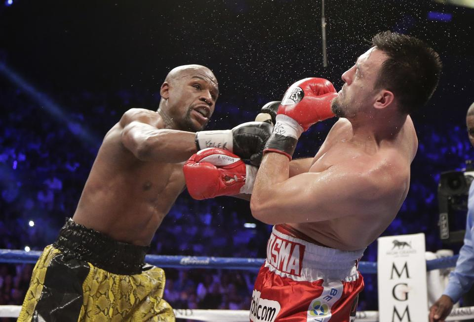 Floyd Mayweather Jr., left, lands a punch against Robert Guerrero in the fourth round during a WBC welterweight title fight, Saturday, May 4, 2013, in Las Vegas. Mayweather won by unanimous decision. (AP Photo/Rick Bowmer)