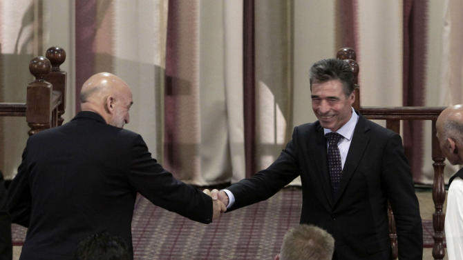 Afghanistan President Hamid Karzai, left, shakes hands with NATO Secretary-General Anders Fogh Rasmussen during a ceremony at a military academy on the outskirts of Kabul, Afghanistan, Tuesday, June 18, 2013. Karzai announced at the ceremony on Tuesday that his country's armed forces are taking over the lead for security nationwide from the U.S.-led NATO coalition. (AP Photo/Rahmat Gul)