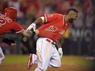 Josh Hamilton (left) tries to rip the jersey off Howie Kendrick after Kendrick's sacrifice fly won the game. (AP)
