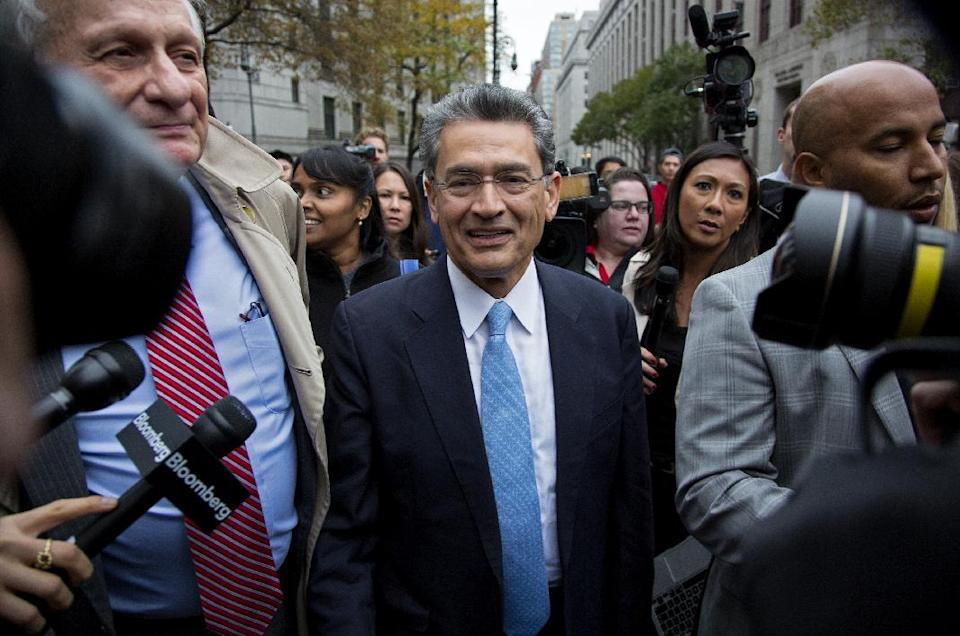 Rajat Gupta, center, leaves federal court in New York on Wednesday, Oct. 24, 2012 after the former Goldman Sachs and Procter & Gamble Co. board member was sentenced Wednesday to 2 years in prison for feeding inside information about board dealings with a billionaire hedge fund owner who was his friend. (AP Photo/Craig Ruttle)