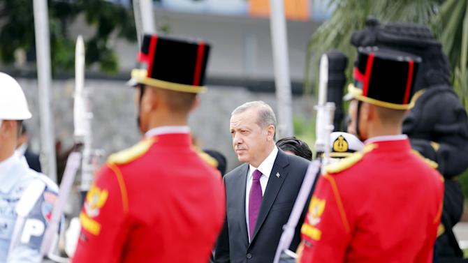 Turkey's President Recep Tayyip Erdogan walks as he departs after finishing his three-day visit to Indonesia, at Halim Air Base in Jakarta, Indonesia,