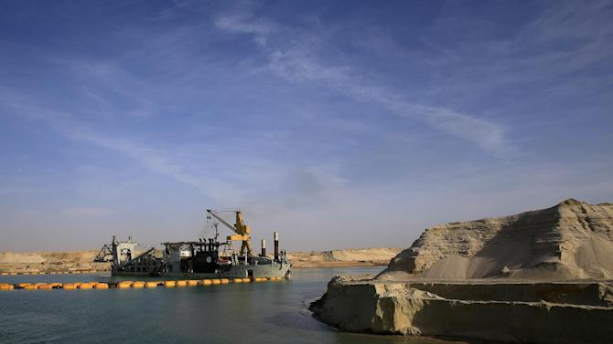 FILE - In this Feb. 4, 2015 file photo, a dredger works on a new section of the Suez canal during a media tour in Ismailia, Egypt. The Suez Canal Authority is in a race to quickly expand the vital waterway for two-way traffic by August 2015. President Abdel-Fattah el-Sissi has made the project a point of nationalist glory, not to mention a cornerstone of plans to revive the economy. But while shippers say more ships may be drawn by shorter waiting times, ambitions to nearly triple revenues depend mainly on growth in the world economy. (AP Photo/Hassan Ammar, File)
