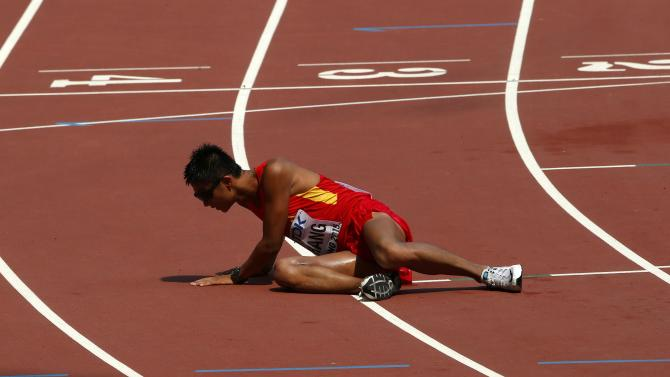 Zhang Lin of China collapses at the finish line in the men's 50 km race walk final during the 15th IAAF World Championships at the National Stadium in Beijing