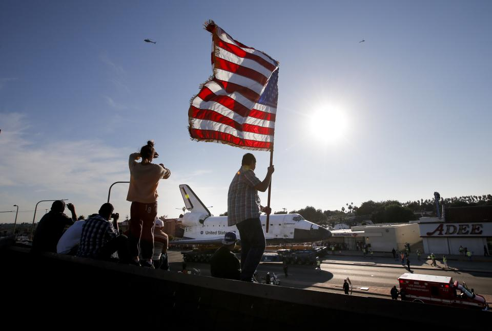 Roni Lopez, center, holds an American flag as the space shuttle Endeavour slowly moves along city streets on a 160-wheeled carrier in Los Angeles, Saturday, Oct. 13, 2012 toward its retirement home at a museum. (AP Photo/Jae C. Hong)