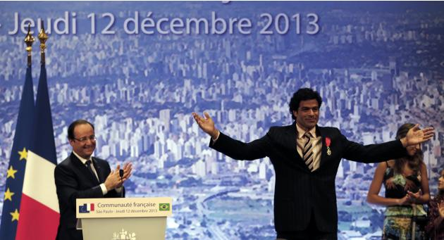 Francois Hollande claps after decorating former PSG soccer star Rai Souza de Oliveira in Sao Paulo