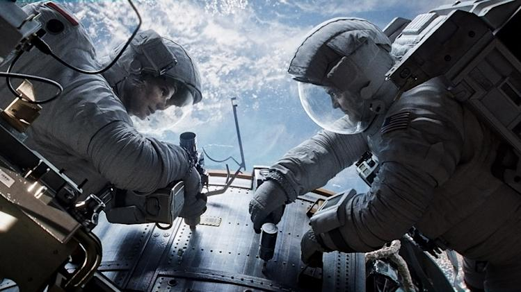 "This publicity photo released by Warner Bros. Pictures shows Sandra Bullock, left, as Dr. Ryan Stone and George Clooney as Matt Kowalsky in ""Gravity."" (AP Photo/Courtesy Warner Bros. Pictures)"