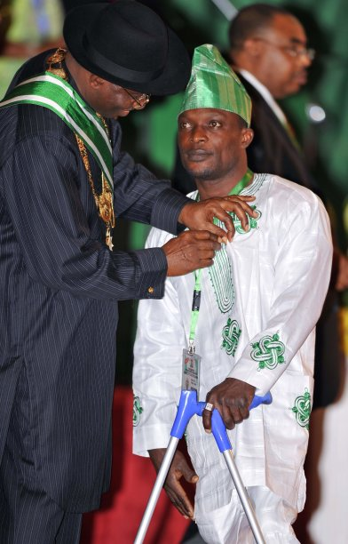 Nigeria's President Jonathan presents a national honours award to disabled athlete Adesokan at an investiture ceremony in the capital Abuja