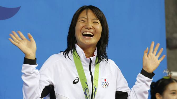 Takemura smiles on the podium at an award ceremony after winning the women's 50m backstroke final swimming competition during the 17th Asian Games in Incheon