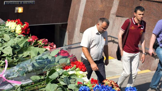 Flowers lay at the entrance to Park Pobedy metro station, the site of a devastating crash, in Moscow, on July 16, 2014