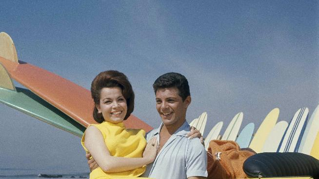 """FILE - In this 1963 file photo, singer Frankie Avalon and actress Annette Funicello are seen on Malibu Beach during filming of """"Beach Party,"""" in California in 1963. Funicello helped create a world as fanciful as Walt Disney's Magic Kingdom when she traded in her Mousketeer ears for a modest one-piece bathing suit . It was a land of perfect waves and sparkling sand, in a place where there was a beach party every night and summer never ended. (AP Photo/File)"""