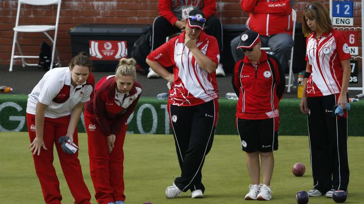 England's Sian Gordon and Jamie-Lea Winch look over the balls with Canada's Leanne Chinery, Mary Ann Beath and Jackie Foster during the first session of Women's Fours Lawn Bowling competition at the Commonwealth Games in Glasgow