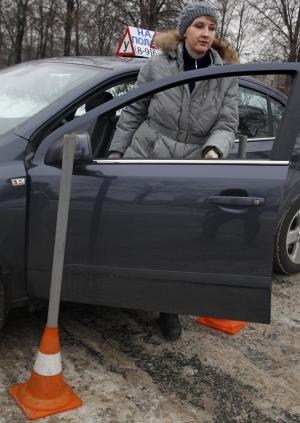 In this photo taken on Monday, Jan. 23, 2012, Natalya Veselova leaves her instructor's car at a driving training ground in the south-east of Moscow, Russia. For Veselova, applying for a driver's license has turned into a frustrating ordeal because she refuses to pay the customary bribe. (AP Photo/Mikhail Metzel)