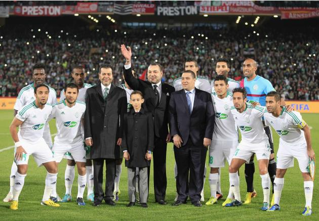 Morocco's King Mohammed VI waves as he poses for a photo with Morocco's Raja Casablanca players at Marrakech stadium