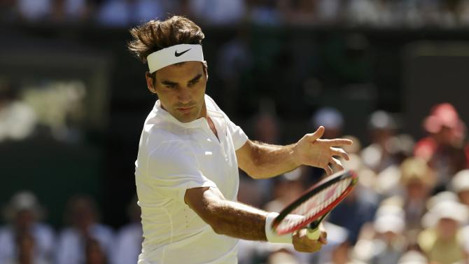 Roger Federer of Switzerland hits a shot during his match against Damir Dzumhur of Bosnia and Herzegovina at the Wimbledon Tennis Championships in London