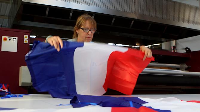 An employee displays a French flag at the Doublet factory, which specializes in making the national flag, in Avelin, near Lille, northern France, Thursday, Nov. 26, 2015. Flying the French flag in a garden — for decades considered bad taste or a symbol of ultranationalism — is now back in favor with the French after the deadly attacks on Paris. (AP Photo/Michel Spingler)