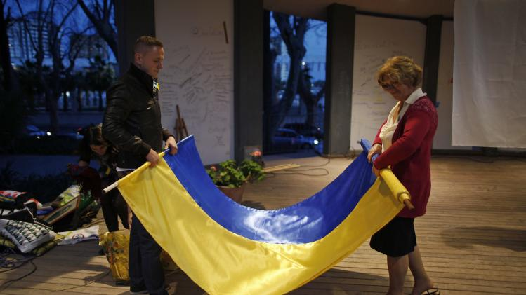 Ukrainians living in Malaga fold a Ukrainian flag after a protest against Russian President Vladimir Putin and in favor of unity and democratic freedom in Ukraine, in downtown Malaga