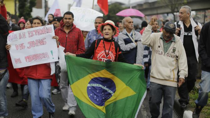 "People a protest in the Capao Redondo neighborhood of Sao Paulo, Brazil, Tuesday, June 25, 2013. Protesters on Tuesday returned to the streets in low-income suburbs of Brazil's biggest city to demand better education, transport and health services, one day after President Dilma Rousseff proposed a wide range of actions to reform Brazil's political system and services. The sign at left reads in Portuguese ""No to the extermination of youth on the periphery!,"" referring to the poor outskirts of the city. (AP Photo/Nelson Antoine)"