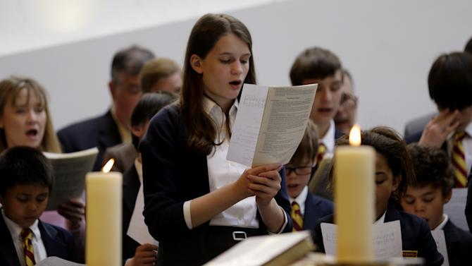 Annie Packard, 13, sings during Trinity Episcopal Church Sunday service at Temple Israel, which allowed the Trinity congregation hold service, Sunday, April 21, 2013, in Boston. Trinity is within the blocked-off area near the finish line of the Boston Marathon, where earlier in the week two bombs exploded. Packard was in the grandstands when the first bomb exploded and ran away in the direction of the second bomb, which went off 10 seconds later. (AP Photo/Julio Cortez)