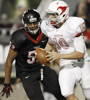 In this Oct. 21, 2011 photo, Trinity's junior defensive lineman Gaius Vaenuku (52) rushes Grapevine junior quarterback Brett Harbin (10) during a high school football game at Pennington Field in Bedford, TX. Texas A&M officials say freshman NCAA college football defensive lineman Polo Manukainiu died in a rollover crash, Monday, July 29, 2013, in New Mexico during a trip home from Utah. New Mexico State Police say Gaius Vaenuku, an incoming member of the Utah football team, also died after the wreck. Manukainiu was a 19-year-old redshirt freshman. (AP Photo/The Fort Worth Star-Telegram, Brandon Wade) MAGS OUT; (FORT WORTH WEEKLY, 360 WEST);