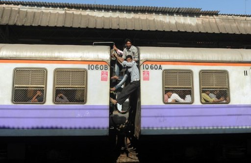 Passengers occupy the space between two train compartments of an overcrowded train in Mumbai on March 14, 2012