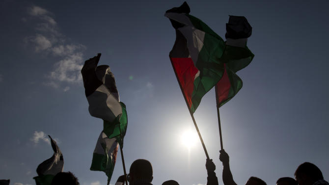 "Arab Israeli protesters wave Palestinians flags as they gather to mark the annual Land Day event in the Arab Village of Dir Hana, northern Israel, Friday, March 30, 2012. About 2,000 Arab-Israeli protesters demonstrated in northern Israel, where a large portion of Israel's Arab minority lives. The ""Land Day"" rallies are an annual event marked by Israeli Arabs and Palestinians in the West Bank and Gaza who protest what they say are discriminatory Israeli land policies. (AP Photo/Ariel Schalit)"