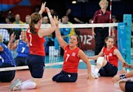 Great Britain's Martine Wright (2nd R) celebrates a point with team-mate Victoria Widdup (L) during their women's sitting volleyball match against Ukraine during the London 2012 Paralympic Games at the ExCel Centre in east London