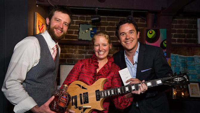 IMAGE DISTRIBUTED FOR CROWN ROYAL - Katie Perkinson, center, shows off a new Gibson guitar, her prize for winning the cocktail competition during the Crown Royal Maple Finished launch party at the Social Restaurant + Wine Bar on Wednesday, Jan. 30, 2013, in Charleston, S.C. At left is mixologist Troy Sidle and at right is Master of Whisky Gerry Graham. (Mic Smith/AP Images for Crown Royal)