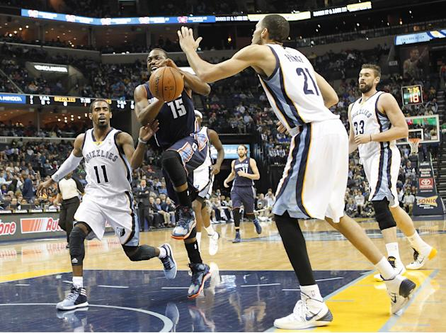 Charlotte Bobcats guard Kemba Walker (15) drives to the basket against Memphis Grizzlies defenders Mike Conley (11), Tayshaun Prince (21) and Marc Gasol (33), of Spain, in the first half of an NBA bas