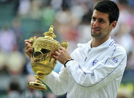 Djokovic holds the trophy after beating Rafael Nadal in last year's Wimbledon men's singles final