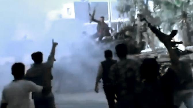In this image made from amateur video released by the Ugarit News and accessed Monday, July 23, 2012, Free Syrian Army soldiers react after destroying two military tanks during clashes with Syrian government troops in Aleppo, Syria. The Syrian regime acknowledged for the first time Monday that it possessed stockpiles of chemical and biological weapons and said it will only use them in case of a foreign attack and never internally against its own citizens. (AP Photo/Ugarit News via AP video) TV OUT, THE ASSOCIATED PRESS CANNOT INDEPENDENTLY VERIFY THE CONTENT, DATE, LOCATION OR AUTHENTICITY OF THIS MATERIAL