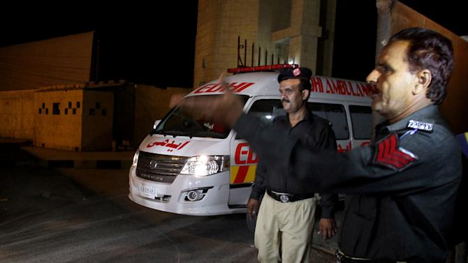 A Pakistani police officer clear the way for an ambulance carrying the lifeless body of Shafqat Hussain, who was convicted of killing a boy, following his execution at the central prison in Karachi, Pakistan, Tuesday, Aug. 4, 2015. Pakistan has executed Tuesday Hussain, convicted of killing a 7-year-old boy in 2004, his family and lawyers said when he himself was 14 years old, officials at Karachi prison said. (AP Photo/Fareed Khan)