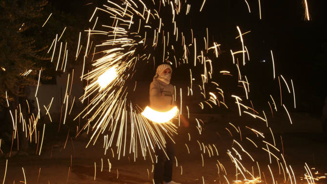 A Palestinian youth plays with fireworks while Palestinian Authority President Mahmoud Abbas speaks to the United Nations General Assembly at the UN headquarters in New York, before the body votes on a resolution to upgrade the status of the Palestinian Authority to a nonmember observer state, in the West Bank city of Nablus, Thursday, Nov. 29, 2012. The Palestinians are certain to win U.N. recognition as a state on Thursday but success could exact a high price: delaying an independent state of Palestine because of Israel's vehement opposition.(AP Photo/Nasser Ishtayeh)