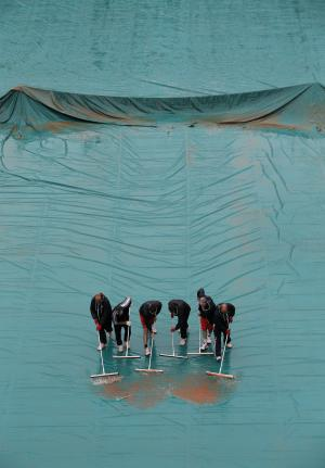 Stadium employees clear water from center court as matches were delayed because of the rain for the French Open tennis tournament at the Roland Garros stadium Tuesday, May 28, 2013 in Paris. (AP Photo/Christophe Ena)