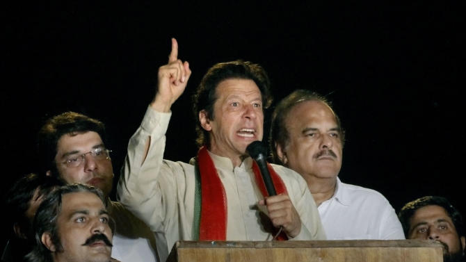 Pakistani cricketer-turned-politician Imran Khan delivers a speech during a protest in Islamabad, Pakistan, Monday, Aug. 18, 2014. Khan on Monday announced to lead thousands of anti-government protesters into the high security 'Red Zone' as his 48 hours deadline for government to step down ending Tuesday. (AP Photo/Anjum Naveed)