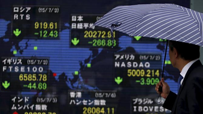 A pedestrian holding an umbrella looks at an electronic board showing the stock market indices of various countries outside a brokerage in Tokyo