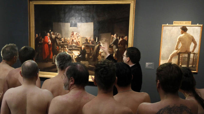 "In this Monday, Feb. 18, 2013 photo, Naked Museum visitors look at pictures of the show ""Nude Men from 1800 to Today"" during a special opening to friends of nudism at the Leopold Museum, Vienna, Austria. The show ""Nude Men from 1800 to Today"" opened its doors from 19 October 2012 to  March  4,2013, looking at how artists have dealt with the theme of male nudity over the centuries. (AP Photo/Ronald Zak)"