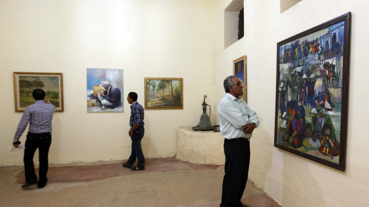 In this Monday, May 7, 2012 photo, visitors look at the paintings during the Babylon Festival of Culture in Hillah, about 60 miles (95 kilometers) south of Baghdad. Poetry has returned to the Triangle of Death. But dancing and singing are being left out of the celebration of culture in post-Saddam Iraq. (AP Photo/Hadi Mizban)