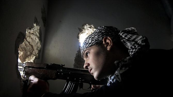 In this Monday, Dec. 10, 2012 photo, a Free Syrian Army fighter aims his weapon during heavy clashes with government forces in Aleppo, Syria. (AP Photo/Narciso Contreras)