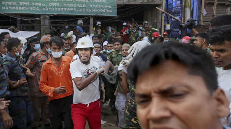 Bangladeshi rescue workers carry a garment worker who was pulled alive from the rubble at the site of a building that collapsed Wednesday in Savar, near Dhaka, Bangladesh, Friday, April 26, 2013.  Crews bored deeper Friday into the wreckage of a garment-factory building that collapsed two days earlier, hoping for miracle rescues that would prevent the death toll from rising much higher, as angry relatives of the missing clashed with police.(AP Photo/Kevin Frayer)