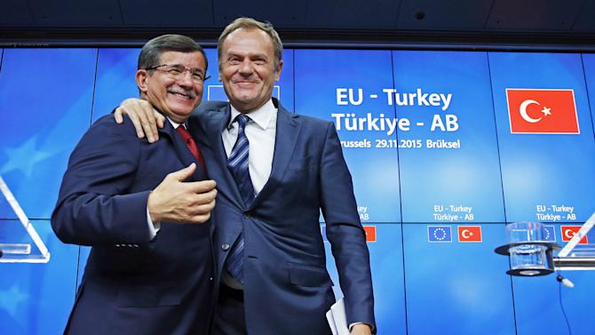 Turkish Prime Minister Ahmet Davutoglu and European Council President Donald Tusk greet each other after a news conference following a EU-Turkey summit in Brussels