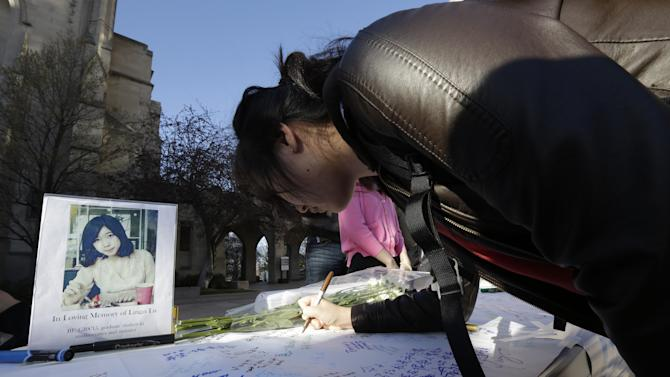 A photograph of Boston University student Lingzi Lu, who was killed in the Boston Marathon explosions, sits on a table as a student writes a message on a board outside the school's Marsh Chapel before a vigil, Wednesday, April 17, 2013, in Boston. The city continues to cope following Monday's explosions near the finish line of the marathon, which claimed three lives. (AP Photo/Julio Cortez)