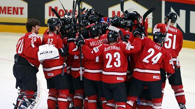 Switzerland's players celebrate their victory over Canada after their 2013 IIHF Ice Hockey World Championship preliminary round match at the Globe Arena in Stockholm (Reuters)