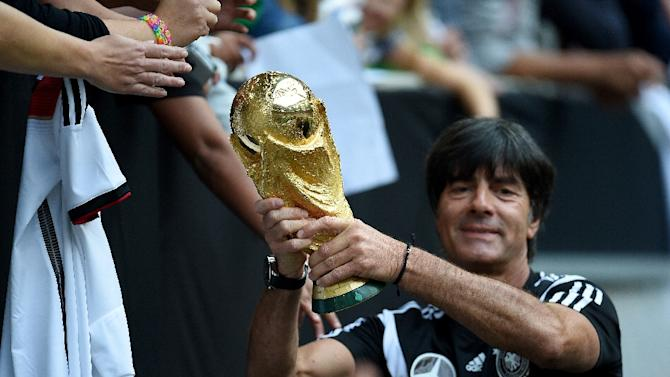 Germany's head coach Joachim Loew shows the World Cup trophy during a public training session of the German national football team in Duesseldorf, Germany on September 1, 2014