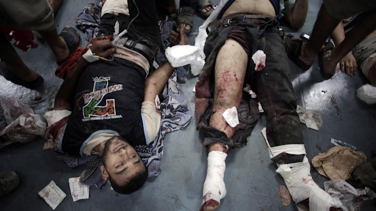 Palestinian men, injured from an Israeli Strike in Shijaiyah neighborhood, lay on the ground waiting to receive treatment, at the emergency room of Shifa Hospital, in Gaza City, Wednesday, July 30, 2014. (AP Photo/Khalil Hamra)