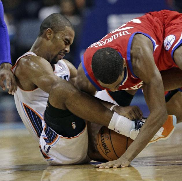 Charlotte Bobcats' Ramon Sessions, left, tries to hold onto the ball as Philadelphia 76ers' Hollis Thompson, right, reaches in during the second half of an NBA basketball game in Charlotte, N.