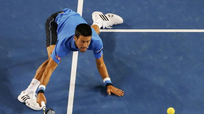 Djokovic of Serbia stretches to hit a return to Wawrinka of Switzerland during their men's singles semi-final match at the Australian Open 2015 tennis tournament in Melbourne