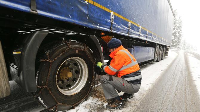 A truck driver removes snow chains from his truck after a snow plough cleared a regional road near Koenigsfeld in the Black Forrest in southern Germany