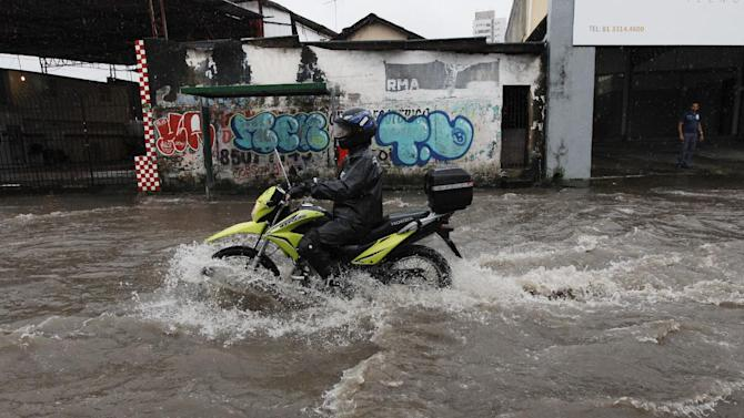 A motorcyclist makes his way down a flooded street after heavy rain storms in Recife, Brazil, Thursday, June 26, 2014. The World Cup soccer match between the USA and Germany will be played at the Arena Pernambuco in Recife today. (AP Photo/Petr David Josek)